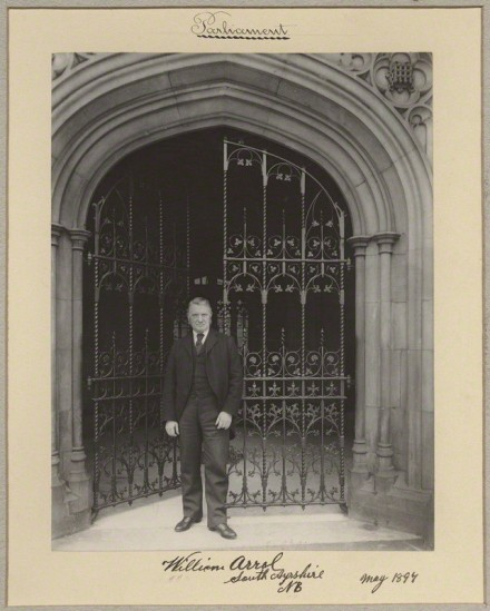 Black and white photograph of Sir William Arrol standing beside gates to the Houses of Parliament