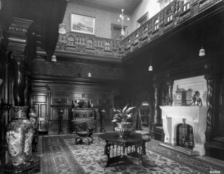 photograph of elaborately furnished, wood panelled hallway with large marble fireplace and carved balustrade