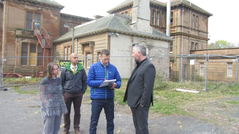 group of 3 people being interviewed outside derelict building