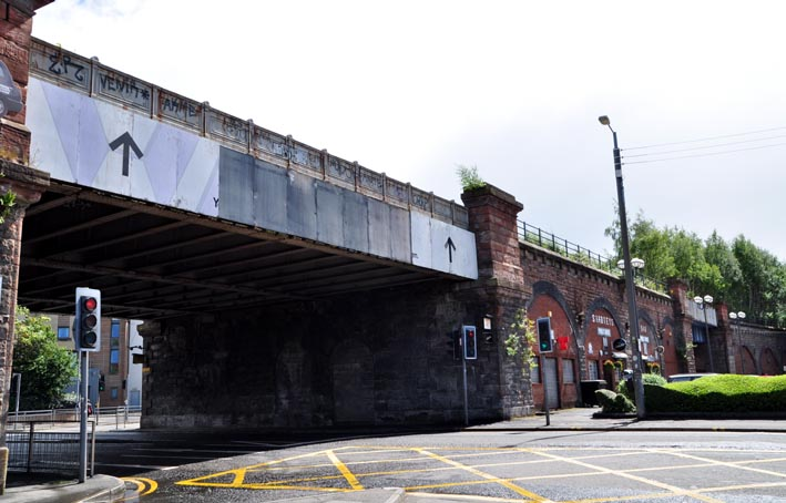 Photograph of a steel railway bridge crossing a roadway with the archways of the stone railway viaduct behind it.