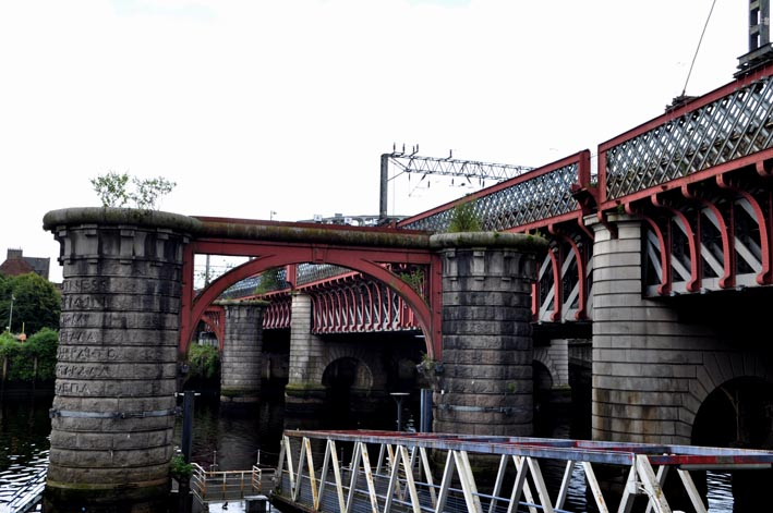 Photograph of railway bridge crossing a river and in front of it are the remaining stone pillars linked by a steel archway.