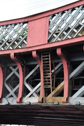 Photograph of a closeup of the latticework parapet of a steel bridge with girders, brackets and cross-supports below.