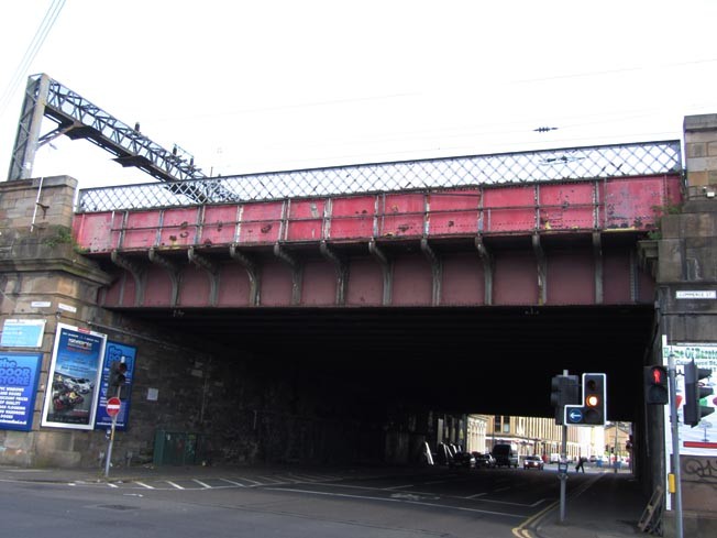 Photograph of a steel railway bridge crossing over a roadway. The sides of the bridge are steel plates with a latticework edging along the top.