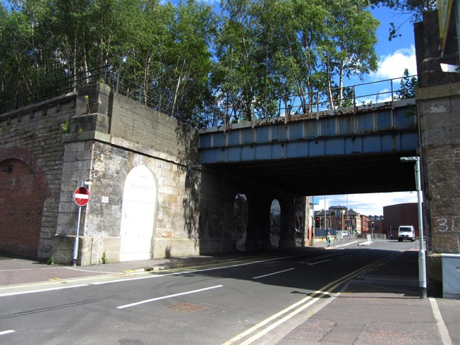Photograph of a steel railway bridge crossing over a road. A gap can be seen in front of the bridge where another bridge has been removed.