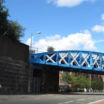 photograph of a bow-shaped steel latticework railway bridge crossing over a roadway