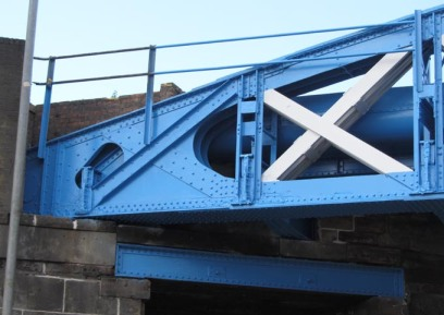photograph of the steelwork of the bridge showing rivetted girders sitting on stone brickwork.
