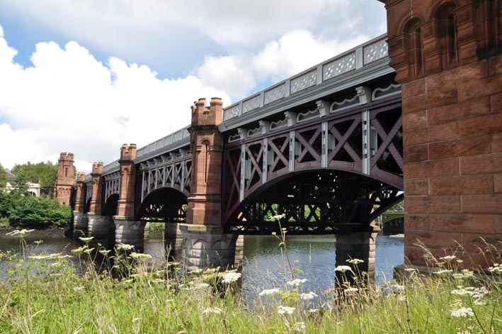 Photograph of an ornate steel bridge crossing a river. The bridge has 5 arches supported on piers with red sandstone castellated towers.