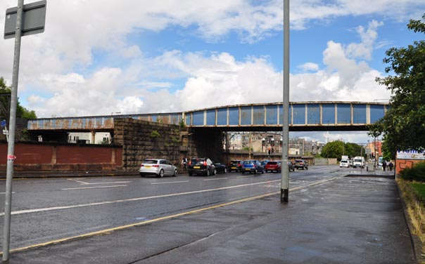 Photograph of a street with an arched steel bridge crossing above it.