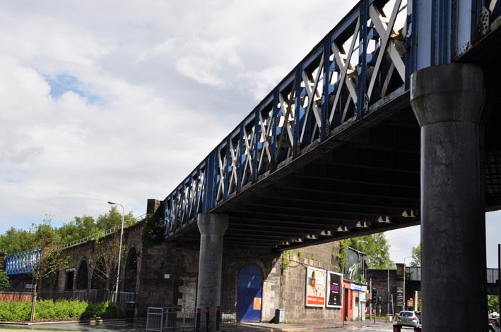 Photograph of a steel latticework railway bridge with 2 steel pillars crossing over a road and curving round towards stone arches of the viaduct.