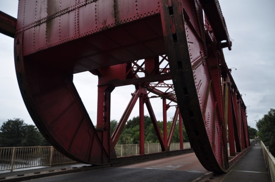 Close-up photograph of the large red rollers of the bridge in the closed position.
