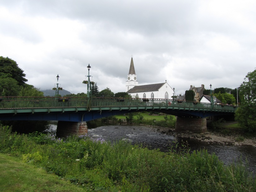 Photograph of green and blue bridge across a river with a white church with spire in the background.