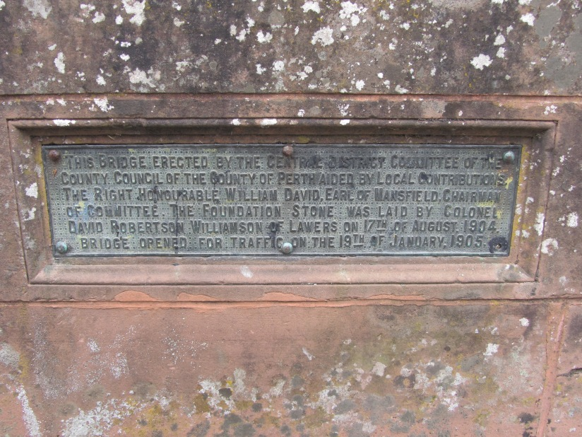 "Plaque with text ""This Bridge erected by the Central District Committee of the County Council of the County of Perth aided by local contributions.  The Right Honourable Willia David, Earl of Mansfield, Chairman of Committee.  The Foundation Stone was laid by Colonel David Robertson Williamson of Lawers on 17th of August 1904.  Bridge opened for traffic on 19th of January 1905."""