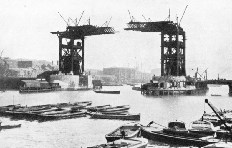 Black and white photograph of the steel towers of Tower Bridge and upper walkways partially built