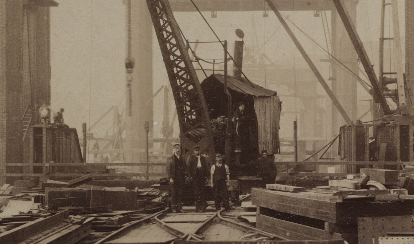 Black and white photograph of 5 men standing beside a crane surrounded by rails and girders