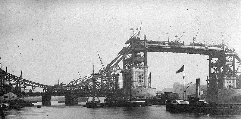 Black and white photograph of the Tower Bridge steel work with the masonry being built around the towers.