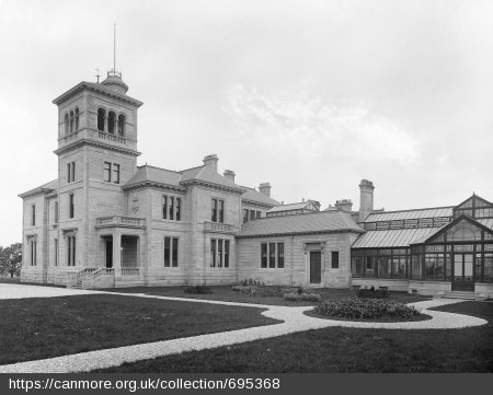 Black and white photograph of large sandstone villa with four-storey tower, large conservatory and garden laid to grass with flower beds and paths.