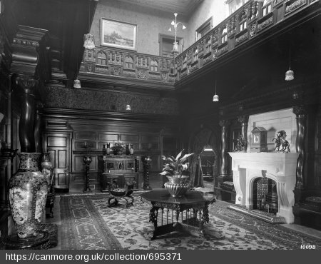 Black and white photograph of large double-height hall dominated by a white fireplace, panelled in wood with decoratively carved ballustrade and filled furniture and ornaments.
