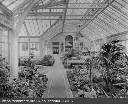 Black and white photograph showing inside of a large conservatory with fountain, fish pond, and plants